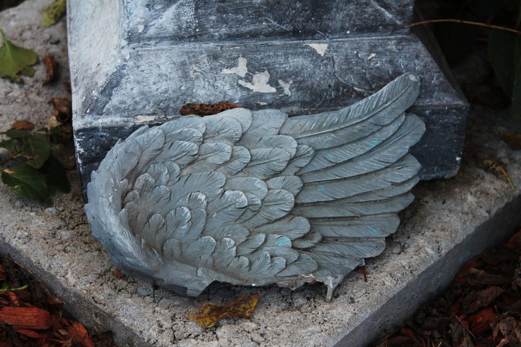 gebrochener Engelsflügel und Grabstein (Symbolbild)